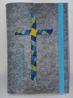 Stickmotiv Mosaikkreuz in blau-petrol-türkis-grün mit Schrift und Gummi in hellblau auf Filz in hellgrau-meliert
