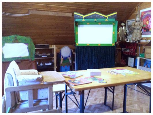 Garderoberaum mit Kinderhochstuhl und Beschäftigungsmöglichkeiten, im Hindergrund die kleinen Probierschattenbühnen.