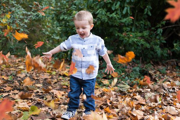Kind spielt im Herbst mit Laub