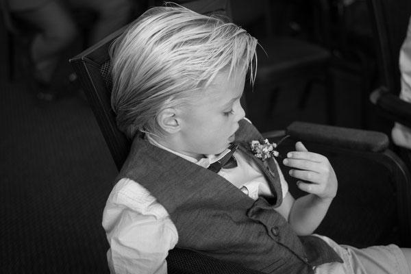 Kind spielt an einer Blume seines Hemdes