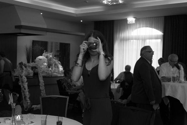 Hochzeitsfotografin wird von einem Gast fotografiert, schwarz weiß