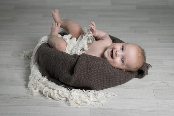 Baby liegt und lacht in die Kamera