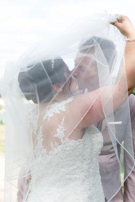Das Brautpaar versteckt sich hinter dem Schleier der Braut und küsst sich