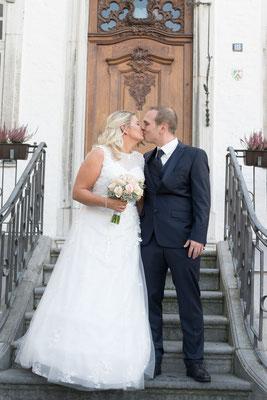 Hochzeitsreportage Brautpaar steht vor dem Standesamt Geilenkirchen und küsst sich