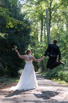 Hochzeitsbild Braut und Bräutigam freuen sich und springen