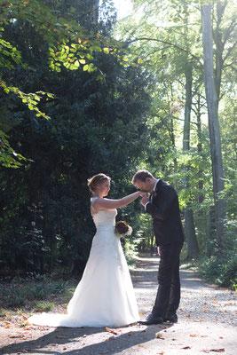 Hochzeitsfotografin fotografiert Brautpaar und Bräutigam küsst Hand der Braut