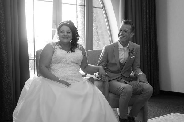 Brautpaar sitzt im Standesamt und lächelt in die Kamera
