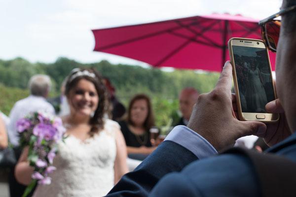 Die Braut wird mit einem Handy vom Gast fotografiert
