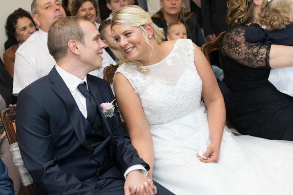 Brautpaar im Standesamt sitzen und halten Händchen
