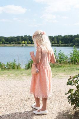Mädchen steht verträumt am See