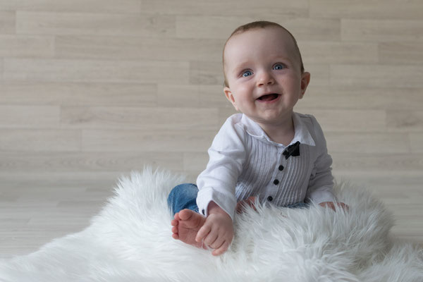 Baby lacht und hält den Fuß fest.