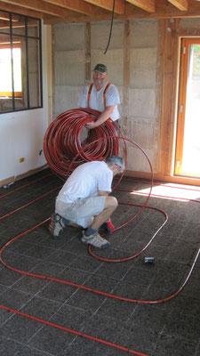 """Pendant que l'un déroule le tuyau,  l'autre le plaque et le fixe au sol avec des agraphes """"sapin"""""""