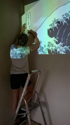 Héléna peint sur le mur de sa chambre