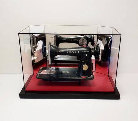 Machine à coudre Singer - Vitrine avec fond en miroirs, socle cuir et bois teinté.