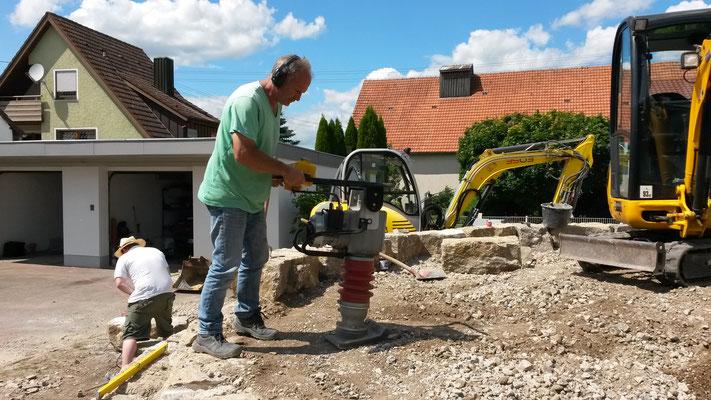 Immer abwechselnd zum Versetzen wird hinter den Steinen Schicht für Schicht frostsicherer Schotter eingebracht und verdichtet.