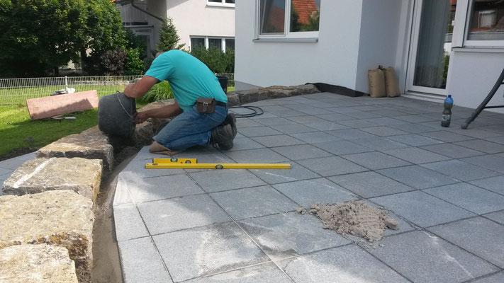 Terrassenplatten wurden verlegt und eingeschnitten. Jetzt werden die äußeren Platten mit einer seitlichen Betonschulter fixiert.