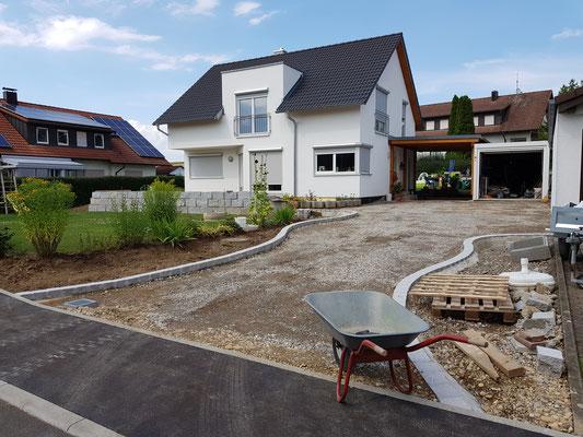 Die Einfassung rechts im Bild dient einem kleinen Steingarten, und auch um die riesige Fläche optisch aufzulockern.