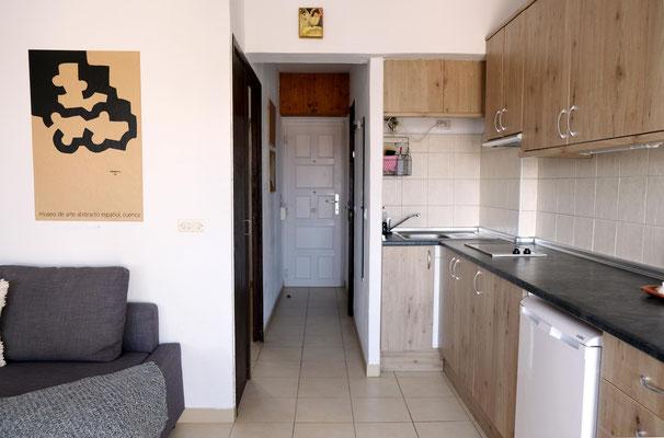 Blick vom Balkon zur Eingangstür, rechts die voll ausgestattete Küchenzeile.