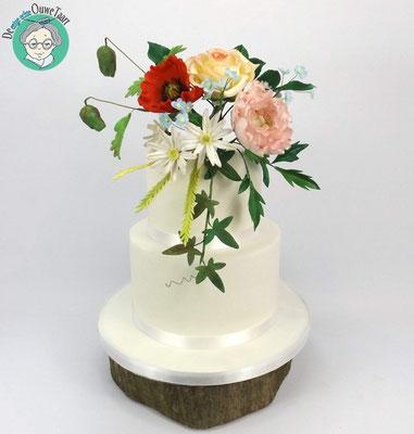 Strakke bruidstaart met veldboeket bloemen suikerwerk