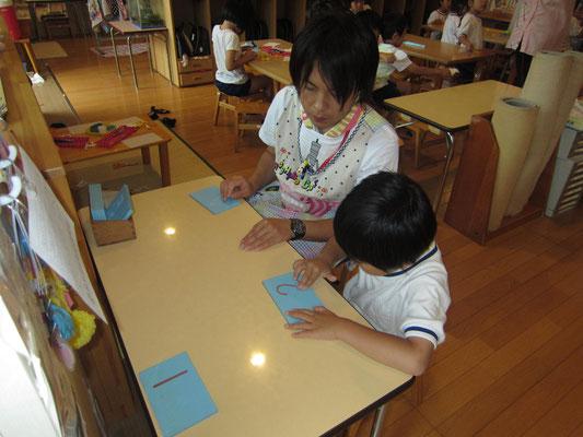 「砂数字板」指先の感覚を使って、数字の書き順を学んでいます。