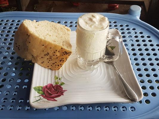 """Petit déjeuner composé d'un grand verre de """"yaourt"""" et d'un morceau de pain. Sans doute très local"""
