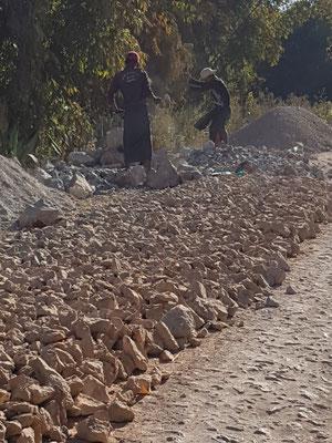Cassage des pierres à la masse avant de les placer à la main sur la chaussée