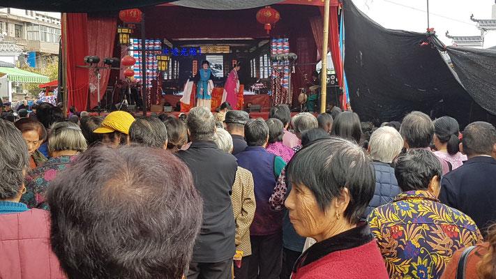 Sur une place. Théâtre traditionnel chinois (Opéra de rue)