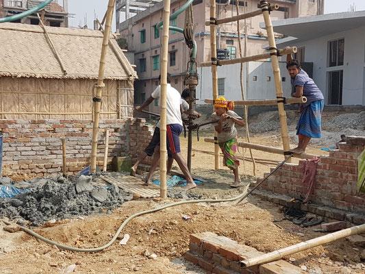 Technique de forage d'un puit dans la banlieue de Dhaka. Trois hommes qui font tourner un tube enfoncé dans le sol, au bout duquel on a fixé une tête fraiseuse