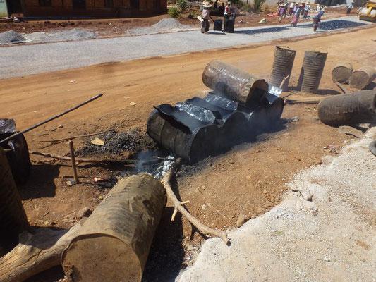 Chauffage du goudron sur le bord de la route et application sur les cailloux à l'aide d'un bidon percé (arrosoir)