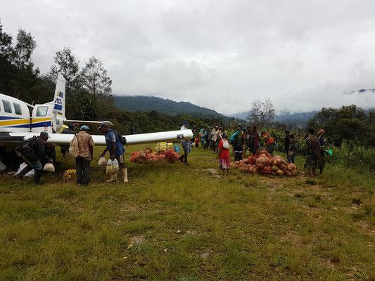Les villageois attendent l'avion pour expédier les légumes récoltés à la ville. Seul transport pour eux pour vendre la marchandise et récolter un peu de monnaie