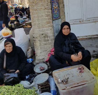 Une femme plume de vide des moineaux qu'elle vend sur le trottoir