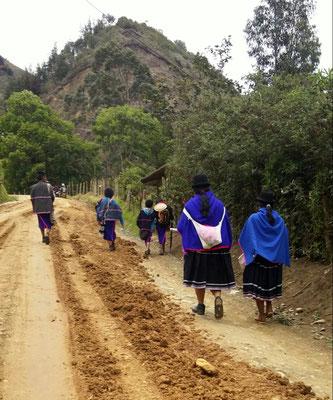 2 femmes, dont l'une a son petit sac de laine dans le dos, et un groupe d'enfants au retour de l'école.