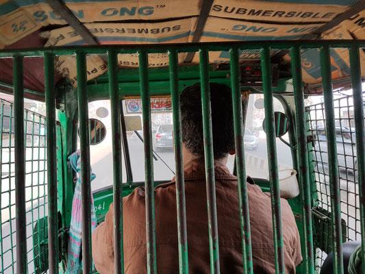 A l'intérieur d'un CNG (auto rickshaw). Chauffeur et passagers sont comme dans une cage. En dehors de la capitale ce même type de véhicule est ouvert