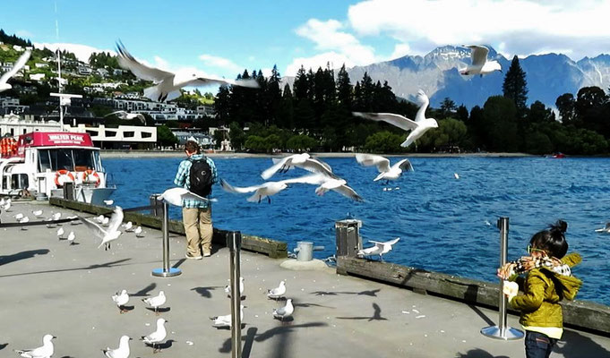 (22) ワカティプ湖の港で、カモメに餌を投げる少女。
