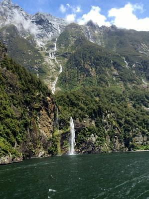 (25) 左手には岩山の頂から流れ落ちる滝。