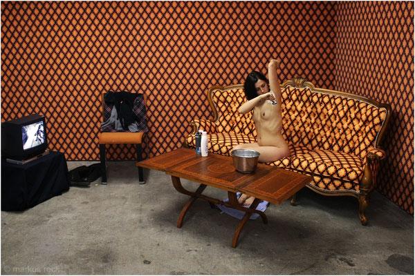 """SOFAPERFORMANCE in der Ausstellungsarchitektur im E-Werk Freiburg - Installation WOHNZIMMERECKE mit AKTTAPETE II (""""Doublebody"""") und """"akträume""""-Sofa"""