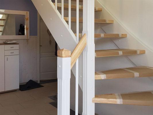 Holztreppe mit gefrästen Pfosten und weißen Elementen