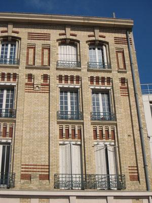 Détail de la façade, montrant les piles en ciment recouvert de briques qui la scandent et lui confèrent sa monumentalité et légèreté.