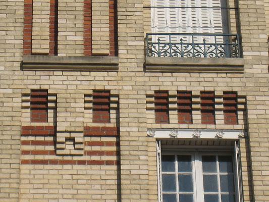 Détail des renfoncements des murs et des modillons soulignés en brique rouge.