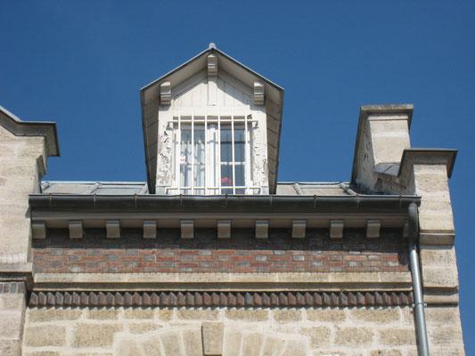 Détail du couronnement. En dessous de la lucarne influencée par la vogue balnéaire, l'un des bandeaux de la construction qui est surmonté par des modillons en briques.
