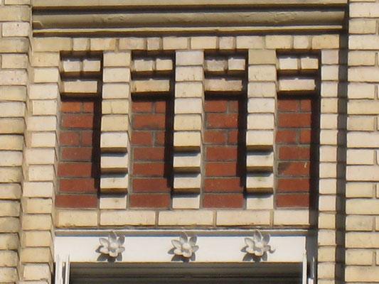 Détail des modillons et d'un linteau métallique (en bas de l'image). Noter la décoration de l'âme (partie verticale) de celui-ci.