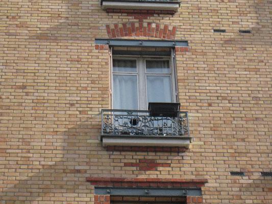 Détail d'un linteau métallique d'une fenêtre située au niveau de la surélévation. Noter l'arc bichrome marqué au dessus de celui-ci, insistant sur le caractère structurel de cette partie.