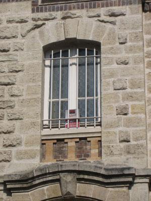 Détail de l'une des fenêtres de l'avant-corps, montrant entre autres les pierres bouchardées et l'allège simulant une balustrade à l'italienne (stylisée).