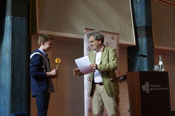 Juror Klaus Humann (Geschäftsführer des Aladin Verlags) gratuliert dem Preisträger der Klassenstufe 7-9, Julius Bleck.