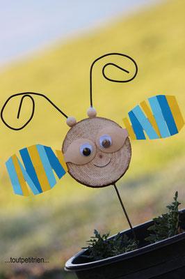 Abeille avec une rondelle de bois, 2 cuillères en bois sur lesquelles nous avons collé des bandelettes de papier et du fil de fer. www.toutpetitrien.ch/bricos/