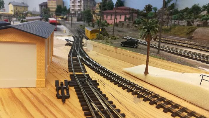 Blick auf den unteren Teil des Depots, das über das Gleis an der Ladestraße angeschlossen wird. links ist das Fahrer Gebäude erkennbar, rechts die Rampe für die Fahrzeugzufahrt, die auf das Niveau des Gleisvorfeld es das Depothauptgebäudes führt.