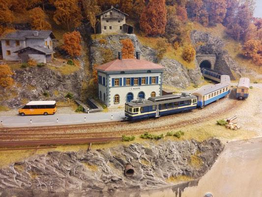 Ein Regionalzug auf Talfahrt passiert die Station St. Maggiore. Am Zugschluß hängt ein Panoramawagen. Er wurde von einer Reisegruppe als Sonderwagen gebucht.