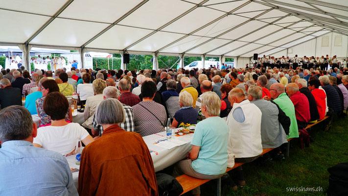 Gottesdienstbesucher sitzen an Festbänken am Kapellfest der Kapelle im Riet bei Oberriet.