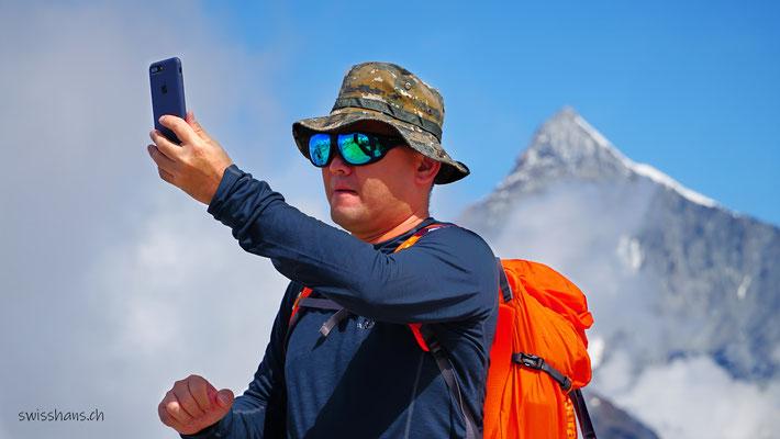 Wanderer mit rotem Rucksack macht ein Selfie auf dem Gornergrat