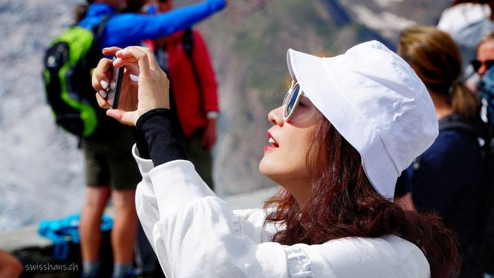 Influencerin auf dem Gornergrat macht ein Foto mit dem Smartphone